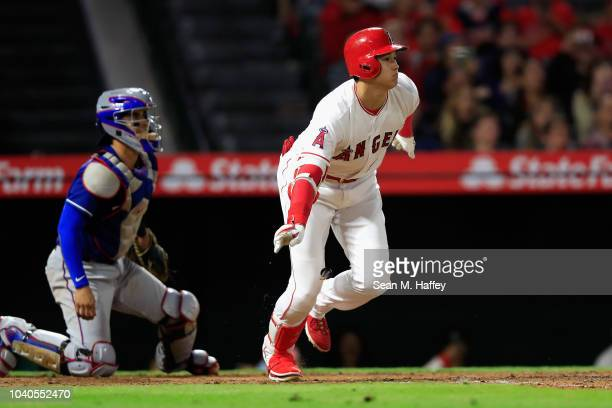 Shohei Ohtani of the Los Angeles Angels of Anaheim tosses his broken bat after hitting an RBI single as Robinson Chirinos of the Texas Rangers looks...