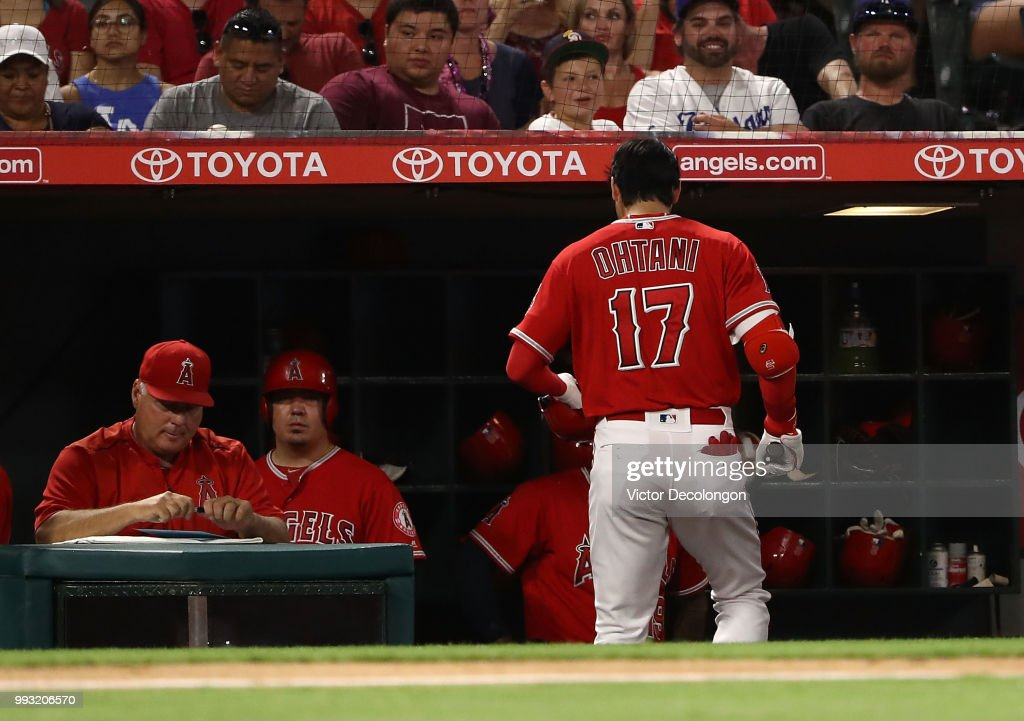 Shohei Ohtani #17 of the Los Angeles Angels of Anaheim walks back into the dugout after striking out in the seventh inning during the MLB game against the Los Angeles Dodgers at Angel Stadium on July 6, 2018 in Anaheim, California. The Angels defeated the Dodgers 3-2.