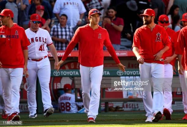Shohei Ohtani of the Los Angeles Angels of Anaheim walks on to the field from the dugout to shake hands with teammates after defeating the Texas...