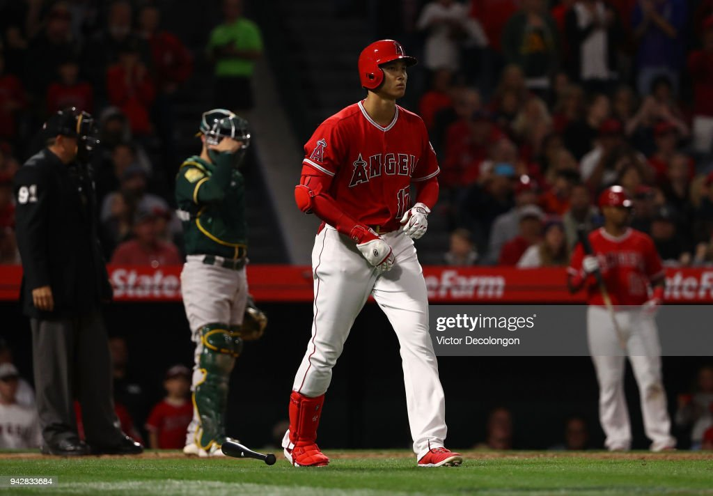 Shohei Ohtani #17 of the Los Angeles Angels of Anaheim walks to first base after drawing an rbi walk in the fifth inning during the MLB game against the Oakland Athletics at Angel Stadium on April 6, 2018 in Anaheim, California.