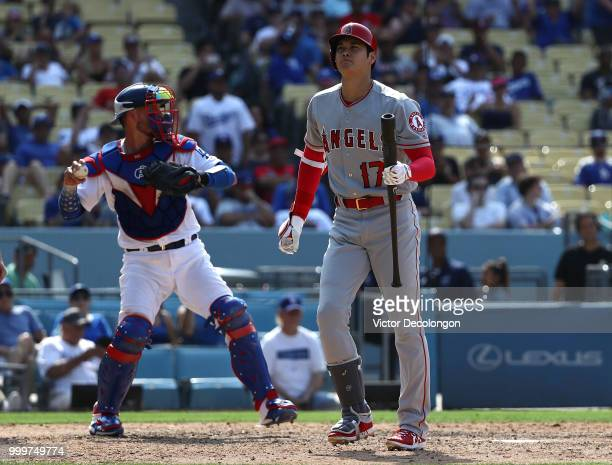 Shohei Ohtani of the Los Angeles Angels of Anaheim walks toward the dugout after striking out swinging in the ninth inning as catcher looks to throw...