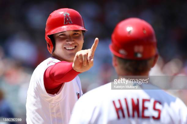 Shohei Ohtani of the Los Angeles Angels reacts to first base coach Bruce Hines during the third inning against the Seattle Mariners at Angel Stadium...
