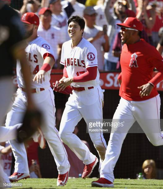 Shohei Ohtani of the Los Angeles Angels runs onto the field with his teammates after the club beat the Oakland Athletics 54 in the season's last game...