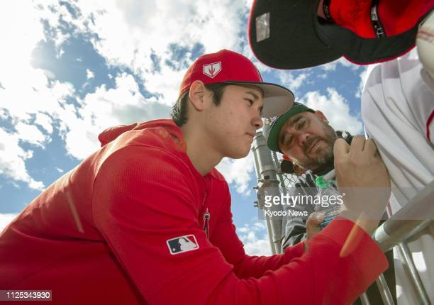 Shohei Ohtani of the Los Angeles Angels signs an autograph for a fan at the club's spring training facility in Tempe Arizona on Feb 16 2019 ==Kyodo