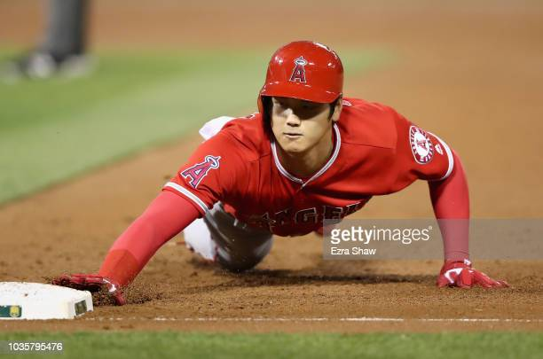 Shohei Ohtani of the Los Angeles Angels slides back to first base in the second inning against the Oakland Athletics at Oakland Alameda Coliseum on...