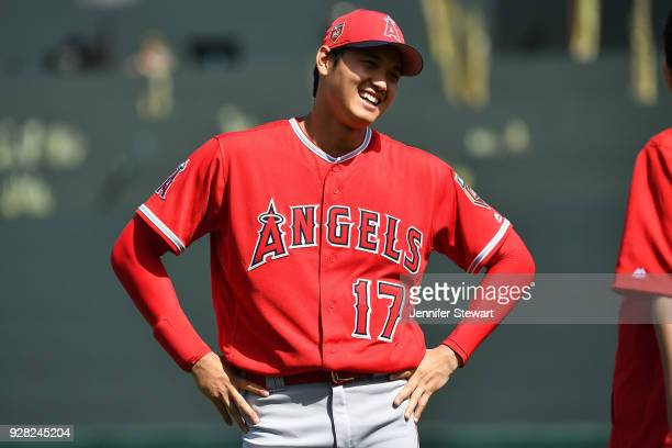 Shohei Ohtani of the Los Angeles Angels smiles while warming up for the spring training game against the Arizona Diamondbacks at Salt River Fields at...