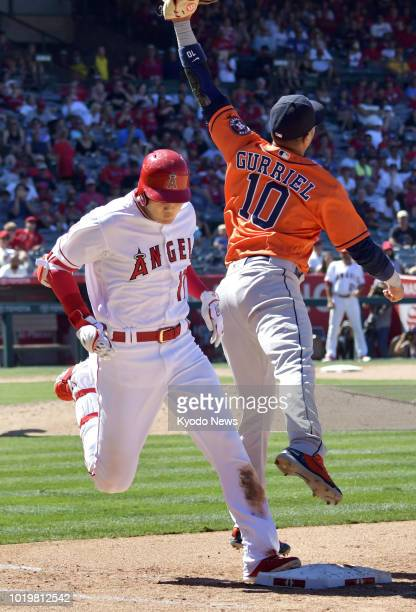 Shohei Ohtani of the Los Angeles Angels steps on first base as Yuli Gurriel of the Houston Astros jumps to catch the ball during the seventh inning...