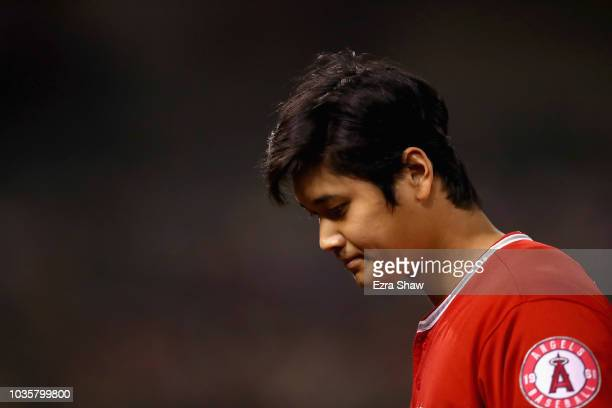 Shohei Ohtani of the Los Angeles Angels walks back to the dugout after flying out in the fourth inning against the Oakland Athletics at Oakland...