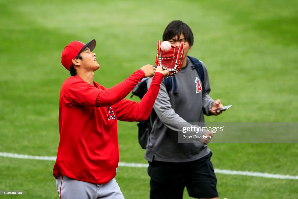 Shohei Ohtani #17 of the Los Angeles Angels walks with his interpreter, Ippie Mizuhara, as he plays catch with himself before the game against the Kansas City Royals at Kauffman Stadium on April 13, 2018 in Kansas City, Missouri.