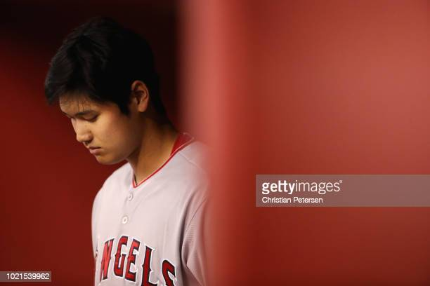 Shohei Ohtani of the Los Angeles Angels warms up in the dugout during the sixth inning of the MLB game against the Arizona Diamondbacks at Chase...
