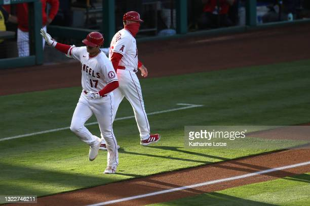 Shohei Ohtani of the Los Angeles Angels waves as he rounds third base after hitting an home run in the first inning against the Kansas City Royals at...