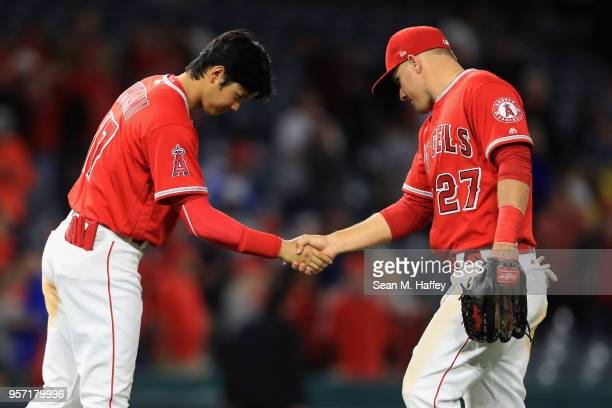 Shohei Ohtani shakes hands with Mike Trout of the Los Angeles Angels of Anaheim after defeating the Minnesota Twins 74 in a game at Angel Stadium on...