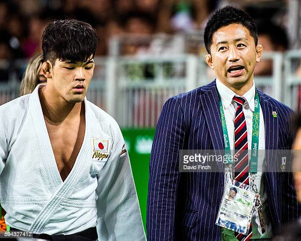Shohei Ono of Japan leaves the mat accompanied by his coach world silver medallist Yusuke Kanamaru after defeating Miguel Murrillo of Costa Rica in...
