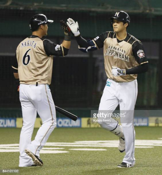 Shohei Otani is congratulated by Sho Nakata after hitting a tworun home run in the first inning of the Nippon Ham Fighters' 92 win over the Seibu...