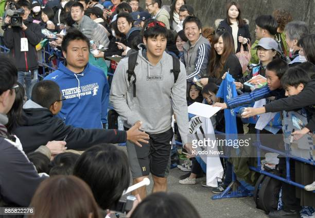 Shohei Otani of the Nippon Ham Fighters leaves a field while surrounded by fans in Nago in Japan's southern island prefecture of Okinawa on Feb 12...