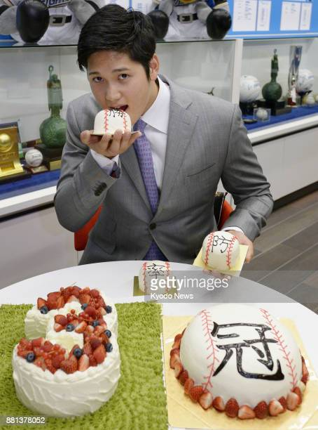 Shohei Otani of the Nippon Ham Fighters poses for a photo at the team's office in Sapporo on Dec 4 with cakes to celebrate leading the Pacific League...