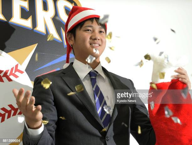 Shohei Otani of the Nippon Ham Fighters poses for photos at the baseball team's office in Sapporo on Dec 3 after signing for 30 million yen for the...