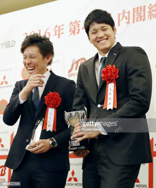 Shohei Otani of the Nippon Ham Fighters smiles with his trophy at a hotel in Tokyo on Dec 20 after he was awarded the grand prize at the Japan Pro...