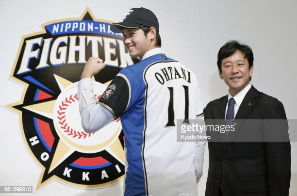 Shohei Otani shows off his uniform during a press conference as he joins the Nippon Ham Fighters on Dec 25 in Sapporo Hokkaido At right is Fighters...