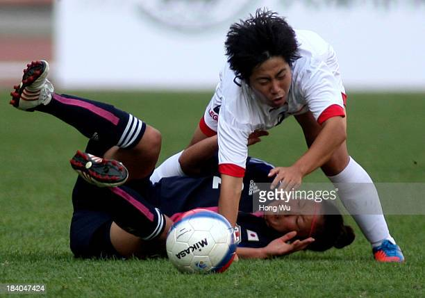 Shoko Chino of Japan competes for the ball with Choe Un Ju of North Korea during the 6th East Asian Games Women's Football match between Japan and...