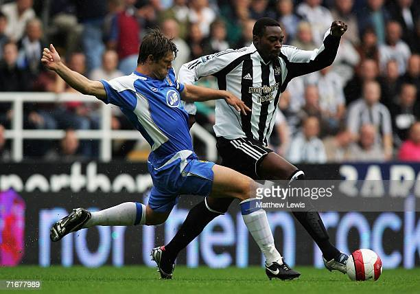 Shola Ameobi of Newcastle holds off the challenge from Arjan De Zeeuw of Wigan during the Barclays Premiership match between Newcastle United and...