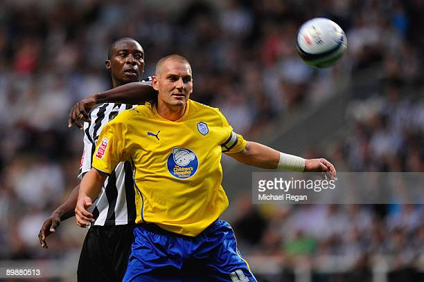 Shola Ameobi of Newcastle is held back by Darren Purse of Sheffield Wednesday during the CocaCola Championship match between Newcastle United and...