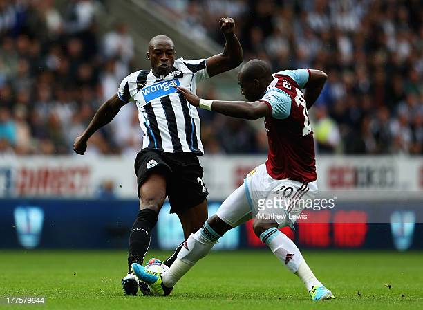 Shola Ameobi of Newcastle United and Guy Demel of West Ham United challenge for the ball during the Barclays Premier League match between Newcastle...