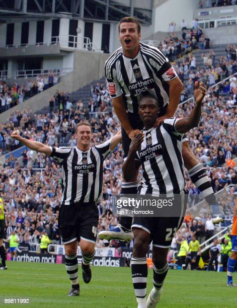 Shola Ameobi of Newcastle United celebrates his opening goal with Steven Taylor and Kevin Nolan during the CocaCola Championship match between...