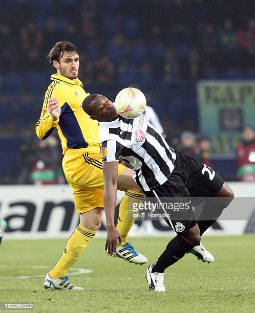 Shola Ameobi of Newcastle United challenges Edmar of Metalist Kharkiv during the UEFA Europa League round of 32 second leg match between FC Metalist...