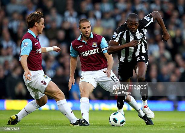 Shola Ameobi of Newcastle United is challenged by Scott Parker and Matthew Upson of West Ham during the Barclays Premier League match between West...