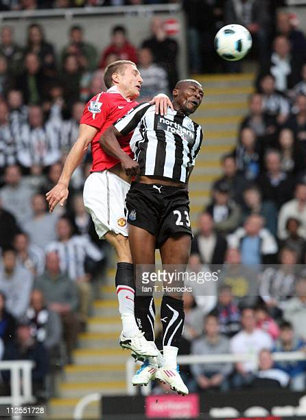 Shola Ameobi of Newcastle United rises with Nemanja Vidic of Manchester United during the Barclays Premier League match between Newcastle United and...
