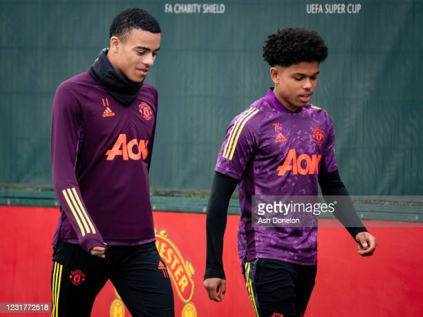 Shola Shoretire of Manchester United chats to Mason Greenwood during a first team training session at Aon Training Complex on March 17, 2021 in...
