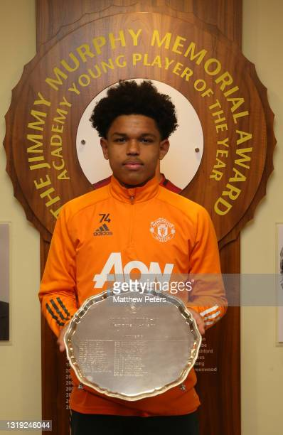 Shola Shoretire of Manchester United poses with the Jimmy Murphy Young Player of the Year award at Aon Training Complex on May 21, 2021 in...