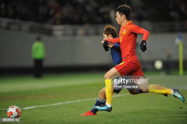 Shoma Doi of Japan and Fu Huan of China compete for the ball during the EAFF E1 Men's Football Championship between Japan and China at Ajinomoto...