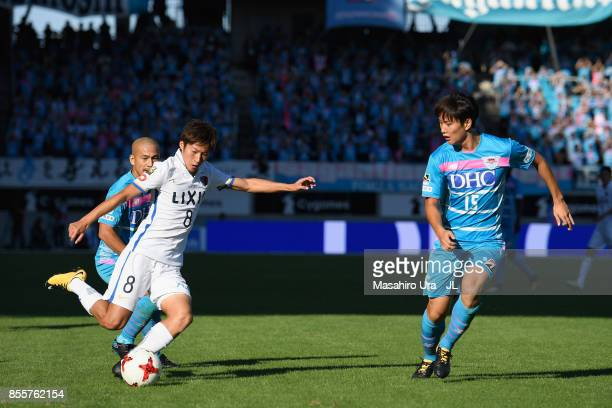 Shoma Doi of Kashima Antlers competes for the ball against Yutaka Yoshida and Jung Seung Hyun of Sagan Tosu during the JLeague J1 match between Sagan...