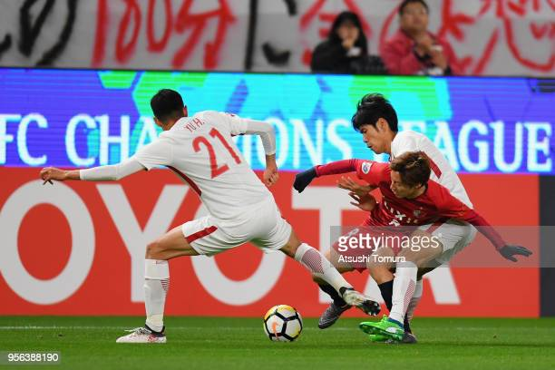 Shoma Doi of Kashima Antlers controls the ball under pressure of Shanghai SIPG defense during the AFC Champions League Round of 16 first leg match...