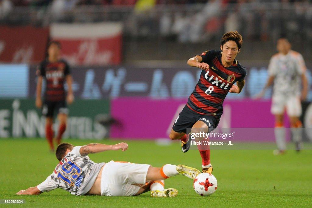 Shoma Doi of Kashima Antlers runs past a tackle by Mitchell Duke of Shimizu S-Pulse during the J.League J1 match between Kashima Antlers and Shimizu S-Pulse at Kashima Soccer Stadium on August 19, 2017 in Kashima, Ibaraki, Japan.