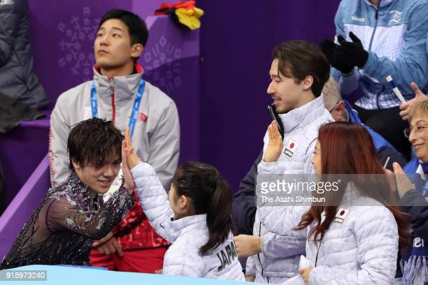 Shoma Uno of Japan high fives with Satoko Miyahara at the kiss and cry after competing in the Figure Skating Team Event Men's Single Skating Short...