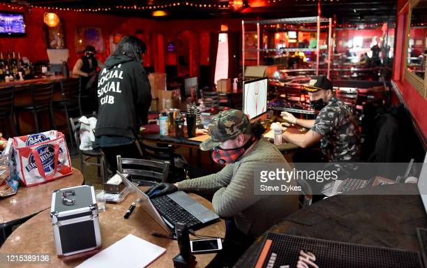 Shon Boulden owner of the Lucky Devil speaks with coowner Josh Svaren as they schedule meal deliveries on March 27 2020 in Portland Oregon The local...