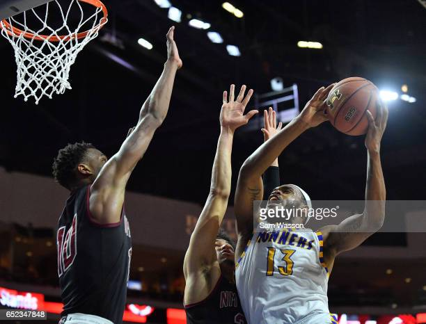 Shon Briggs of the Cal State Bakersfield Roadrunners shoots against Eli Chuha and Jemerrio Jones of the New Mexico State Aggies during the...