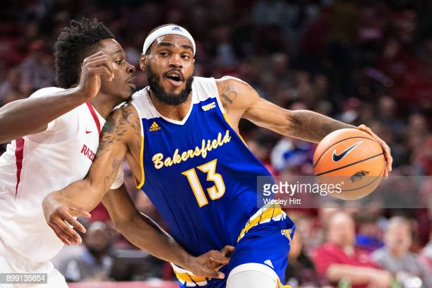 Shon Briggs of the CSUBakersfield Roadrunners drives to the basket against Adrio Bailey of the Arkansas Razorbacks at Bud Walton Arena on December 27...