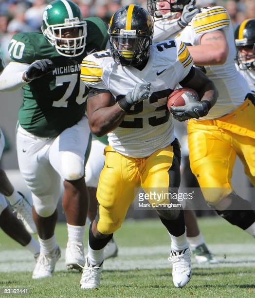 Shonn Greene of the Iowa Hawkeyes carries the ball past Oren Wilson of the Michigan State Spartans on October 4, 2008 at Spartan Stadium in East...