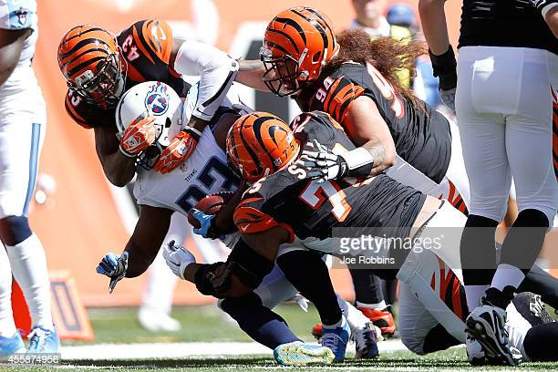 Shonn Greene of the Tennessee Titans is tackled by George Iloka Devon Still and Domata Peko all of the Cincinnati Bengals during the second quarter...
