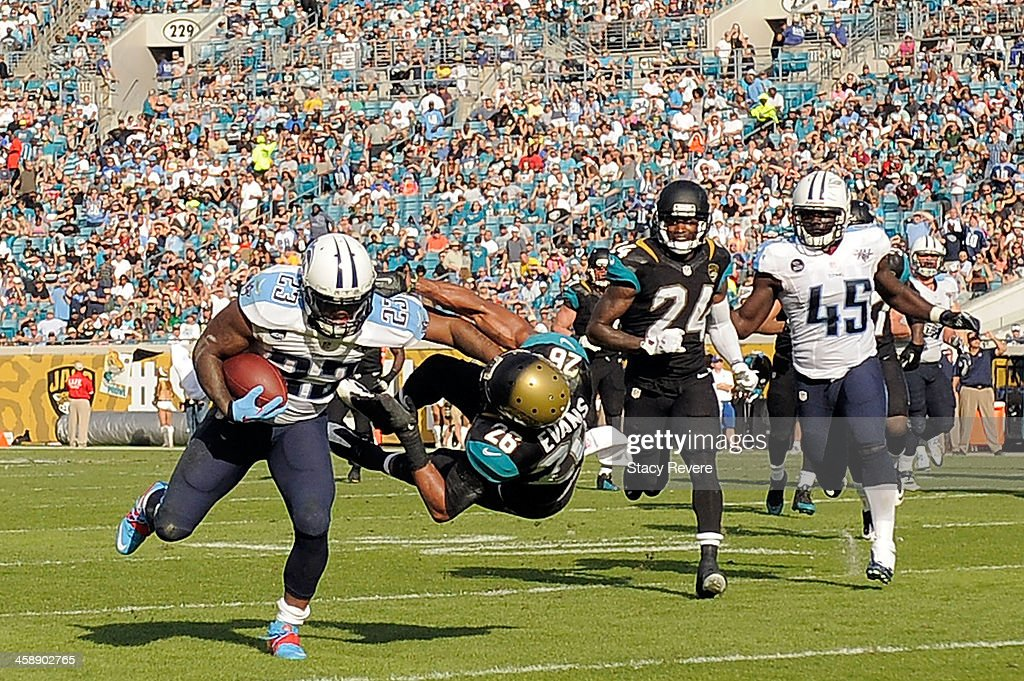 Shonn Greene #23 of the Tennessee Titans runs through Josh Evans #26 of the Jacksonville Jaguars during a game at EverBank Field on December 22, 2013 in Jacksonville, Florida. Tennessee won the game 20-16.