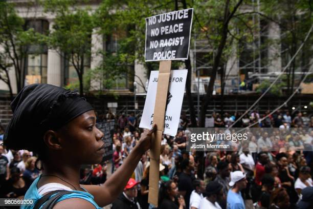 Shonta Hester of Rankin holds a sign as she joins more than 200 people gathered for a rally to protest the fatal shooting of an unarmed black teen at...