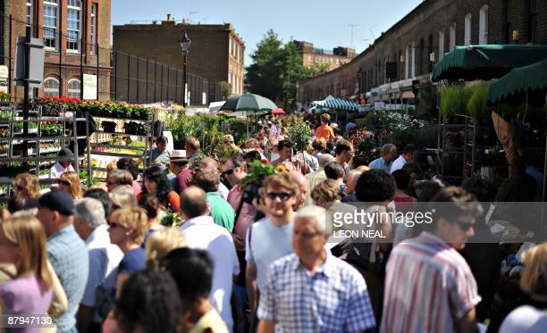 Shoopers fill the Columbia Road flower market in East London as summer weather hit the United Kingdom on May 24 2009 AFP PHOTO/Leon Neal