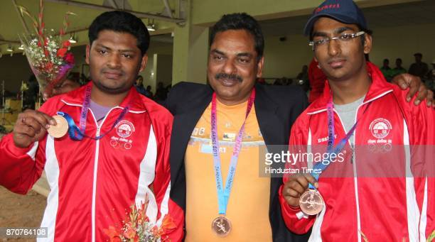 Shooter Ashok Mittal along with his sons Anjan Mittal and Ankur Mittal of Haryana showing their medal after winning the Bronze medal in 10meter Air...
