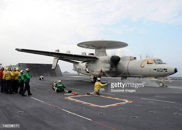 A shooter signals the launch of an E-2C Hawkeye aboard USS Abraham Lincoln.