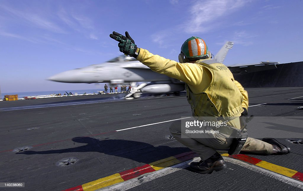 A shooter signals the launch of an F/A-18 Super Hornet. : Stock Photo