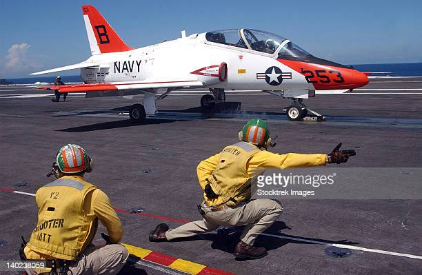 A shooter signlas the launch of a T-45A Goshawk trainer aircraft.